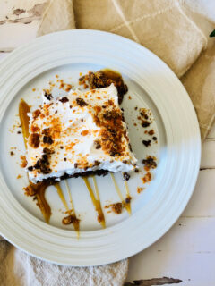 a slice of butterfinger poke cake on a white plate