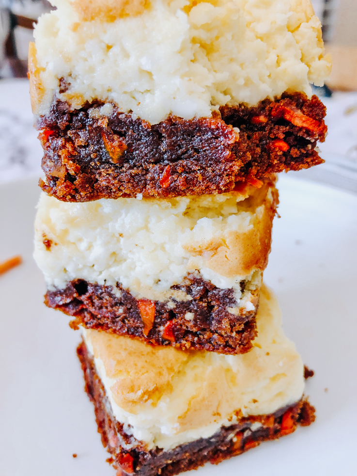 A stack of carrot cheesecake bars on a white plate