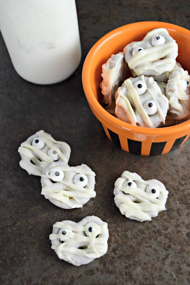 Halloween Mummy Pretzels are a yummy treat for your little goblins. The sweet of the white chocolate mixed with the saltiness of the pretzel makes for one tasty bite. Perfect for your next Halloween party!