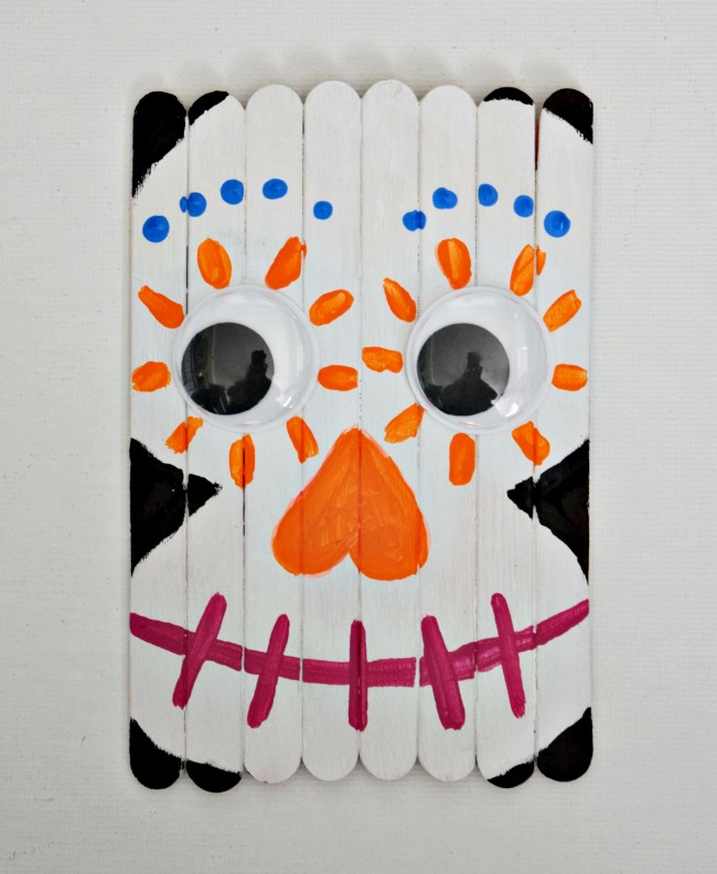 Celebrate the Day of the Dead with this fun and colorful Popsicle Stick Sugar Skull. A great craft for the new Disney movie, Coco!