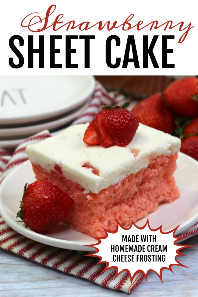 Photo of a piece of Strawberry Sheet Cake on a white plate, layered on top is a sliced strawberry.