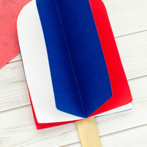 This photo features a popsicle stick popsicle craft. It uses red, white, and blue card stock paper to make a 3D popsicle.