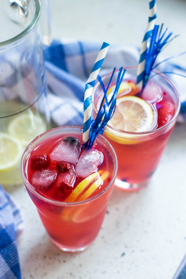 This photo features a summer berry lemonade recipe. There is 2 glasses filled with the beverage with ice cubes, and extra fruit in the glass. There is a blue and white straw in the glass and they are sitting next to a pitcher of the drink.