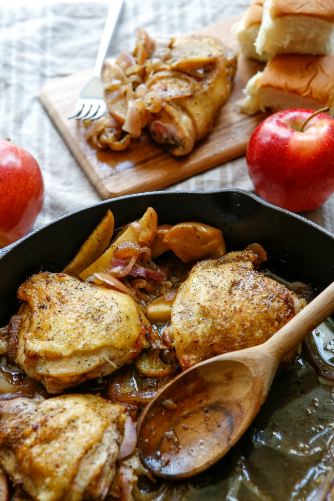 This photo features apple cider chicken in a skillet. Off to the side is a couple of apples and one of the thighs placed on a tray.