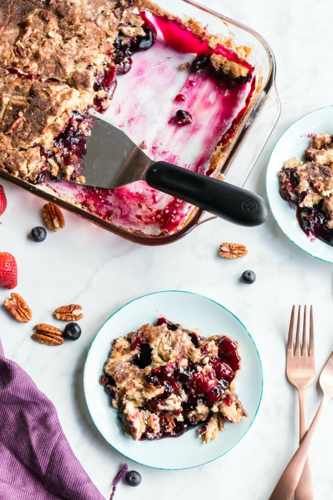 This photo features a pan of Mixed Berry Dump Cake with half of it gone and a portion placed on a plate.