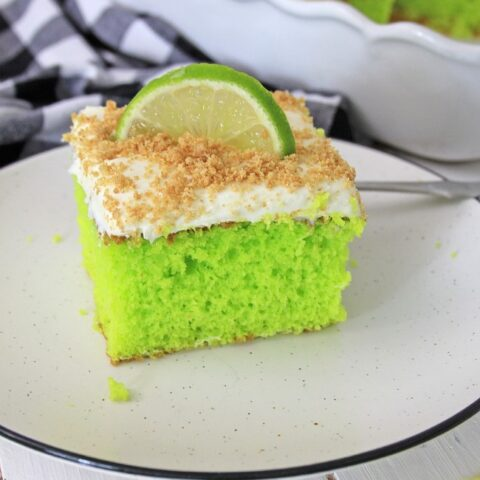 This photo features a piece of Key Lime Cake on a white plate. It has a slice of key lime as a garnish with some crushed graham crackers on top.