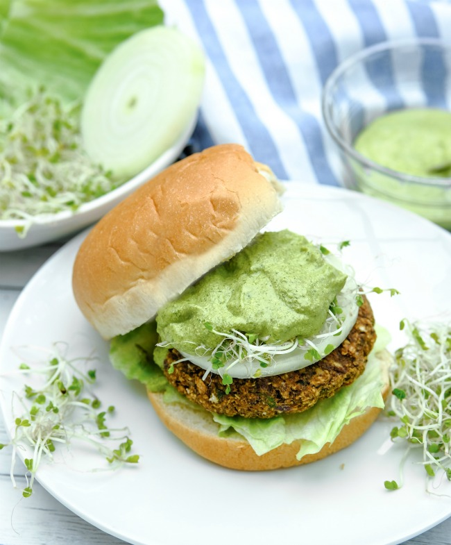 This photo features black bean burgers topped with lettuce, onion, fresh parsley, and  Chimichurri sauce.