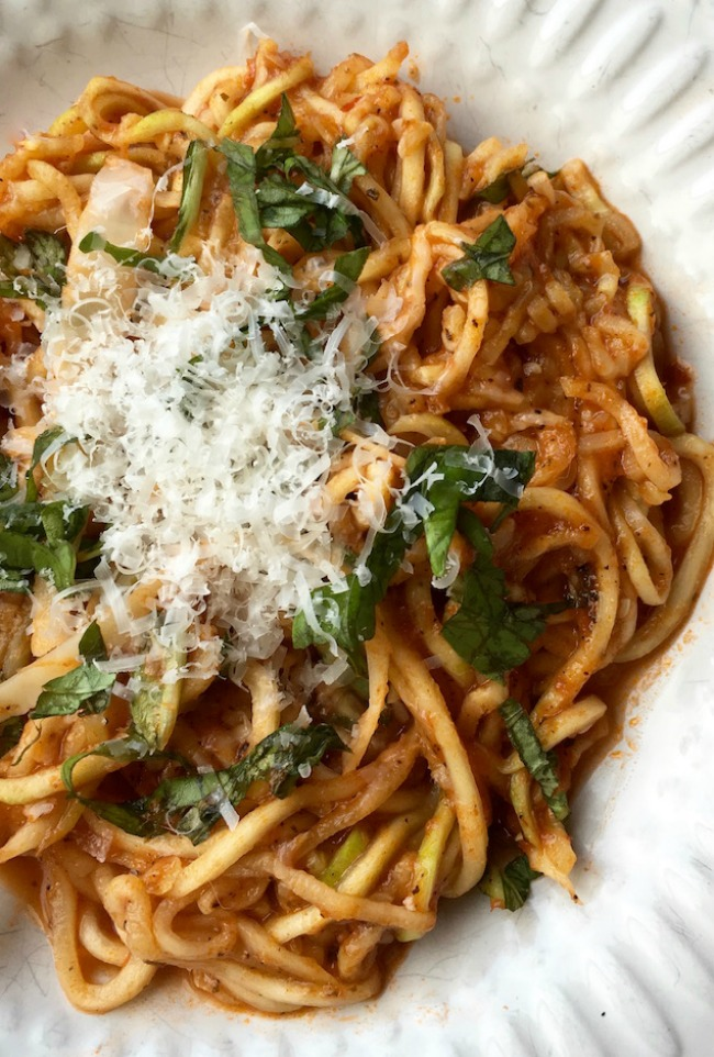 This photo features a white plate full of arrabbiata sauce with zucchini noodles topped with freshly grated parmesan.