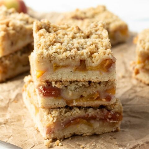 This photo features a stack of peach crumble bars sitting on a crumbled brown paper bag.