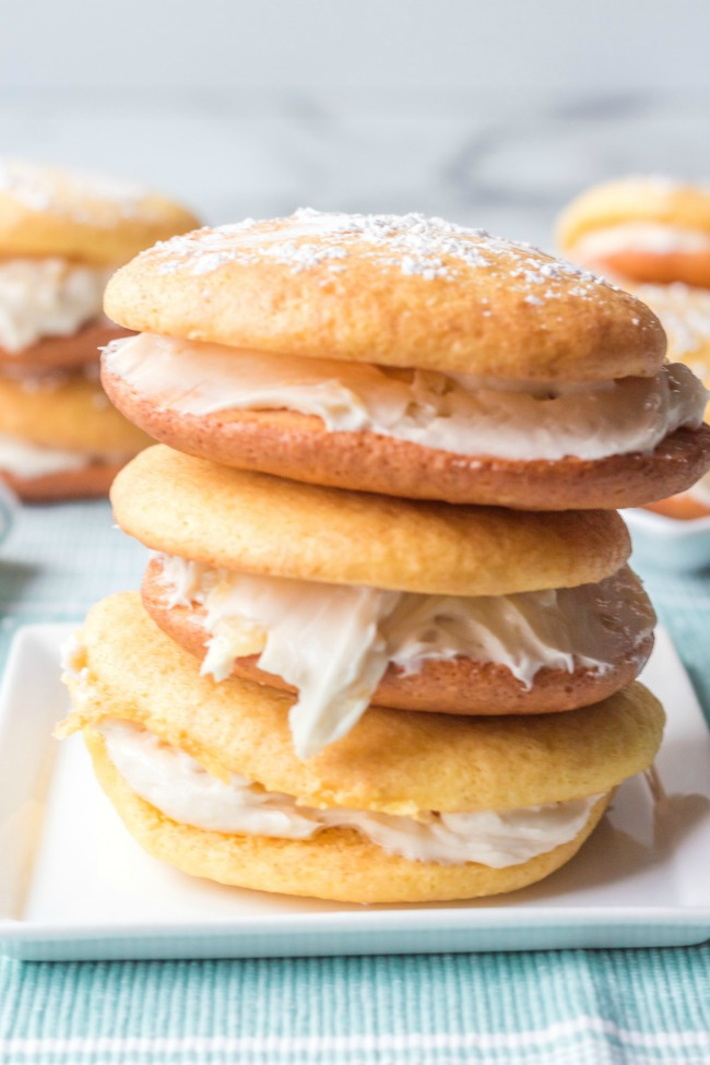 This photo features a plate with pineapple cake mix whoopie pies stacked on top of each other.