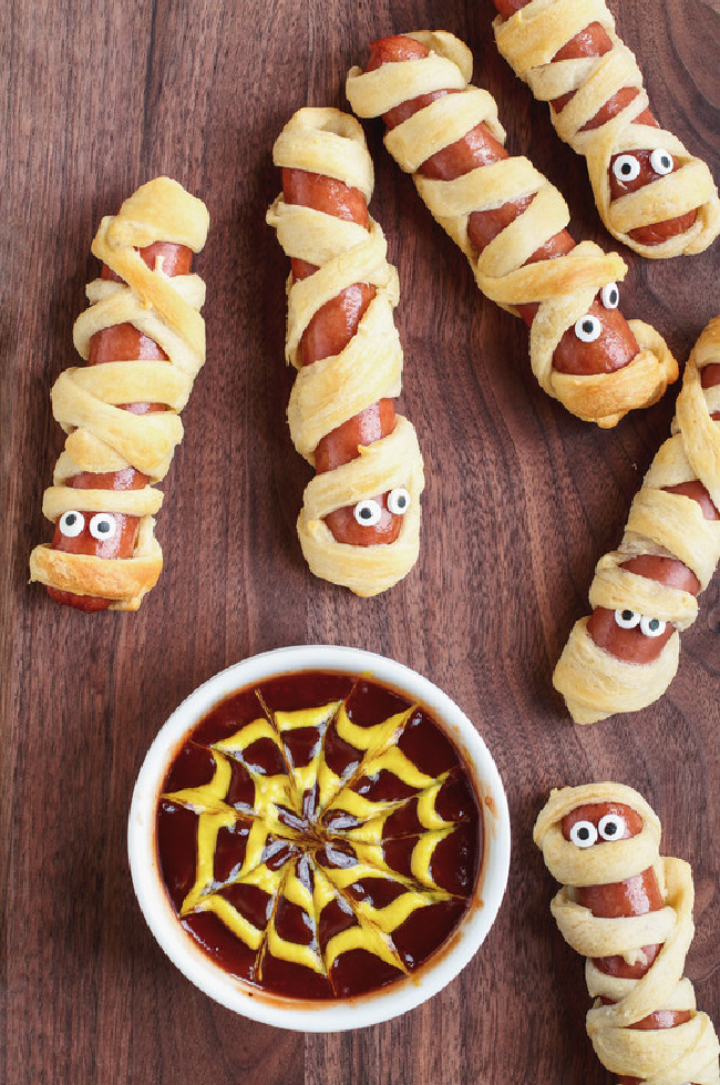 This photo features wrapped hot dogs in puff pastry. They are made to look like mummy dogs. On the side is a dish of ketchup and mustard. The mustard is swirled to look like a spider web.