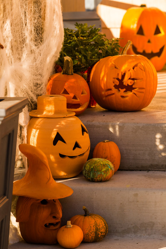 This photo features several carved pumpkins and terracotta pumpkins sitting on a front porch. A way to celebrate Halloween at home!