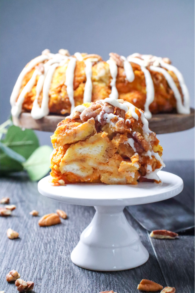This photo features a Pumpkin Pecan Monkey Bread sitting in the background on a wooden pedestal. A slice of the bread has been taken out and on a smaller white pedestal in the foreground.