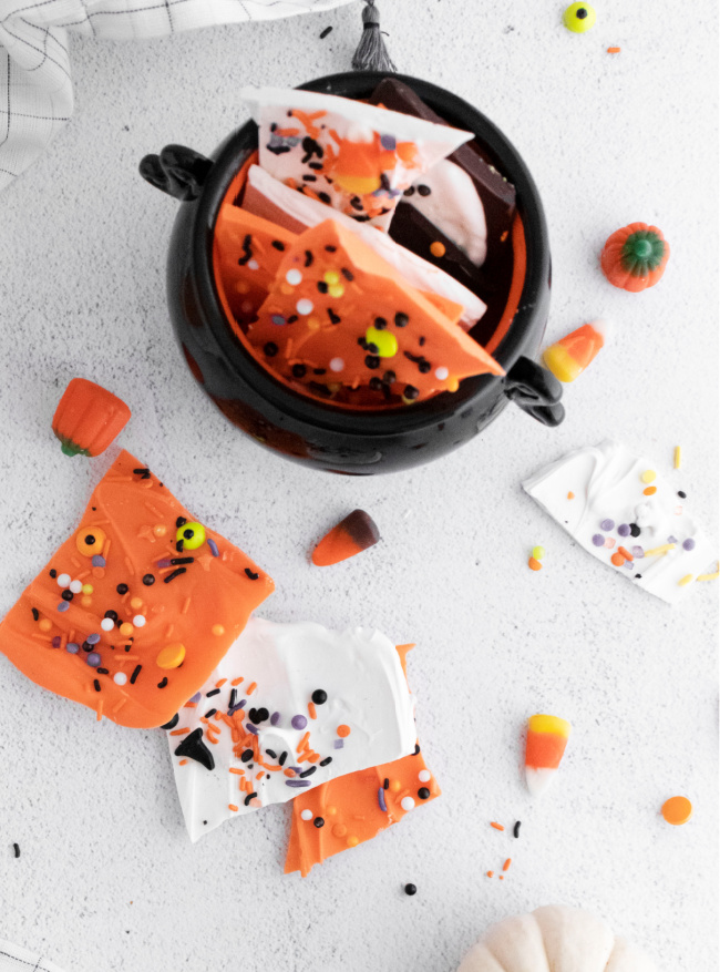 This photo features various versions of Halloween Candy Bark, some sitting on the table and others stacked in a cauldron candy dish.