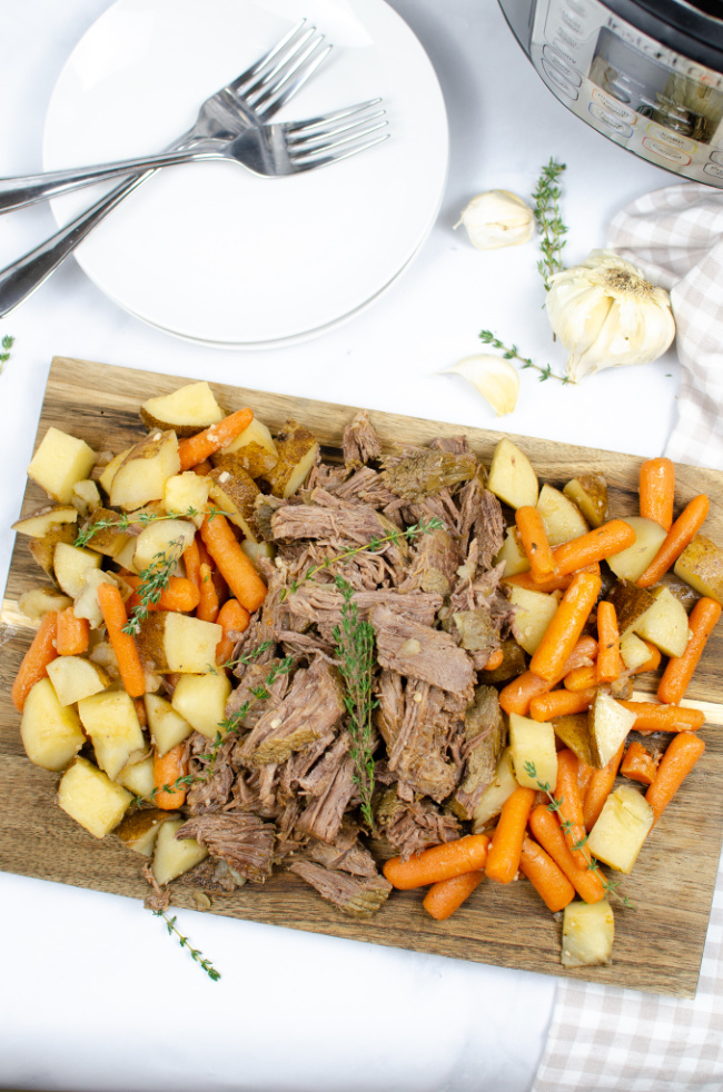 This photo features a cutting board topped with pot roast and all the veggie sides.