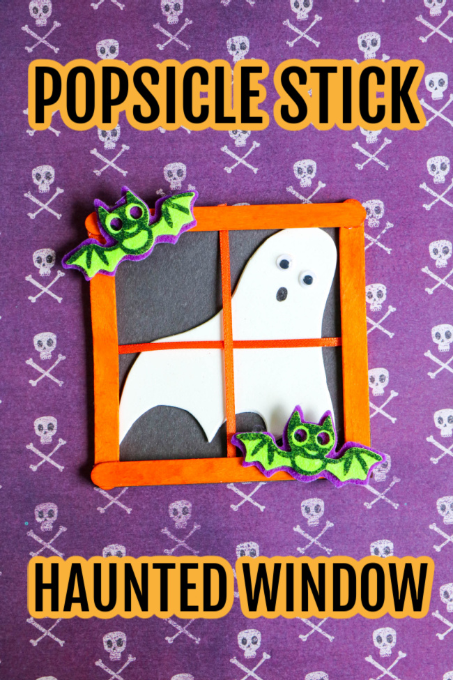 This image features a Halloween craft for kids at looks like a popsicle stick haunted window. It is laying on top of Halloween skull craft paper.