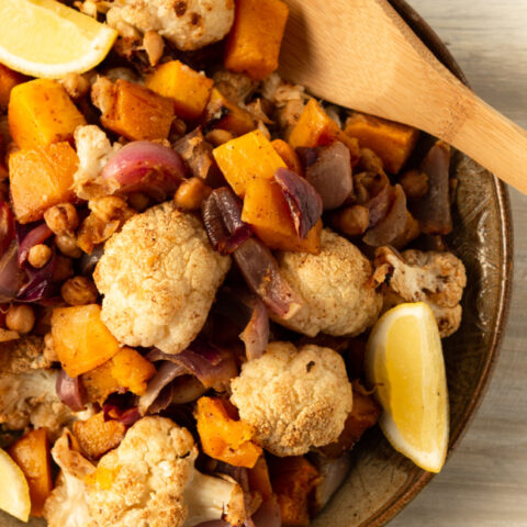 This photo features a plate of roasted butternut squash and cauliflower side dish.