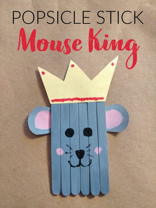 This photo features a popsicle stick mouse king craft that was created by kids placed on top of a brown background.