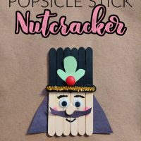 This photo features a popsicle stick nutcracker made out of craft sticks and made for kids to make during Christmastime.