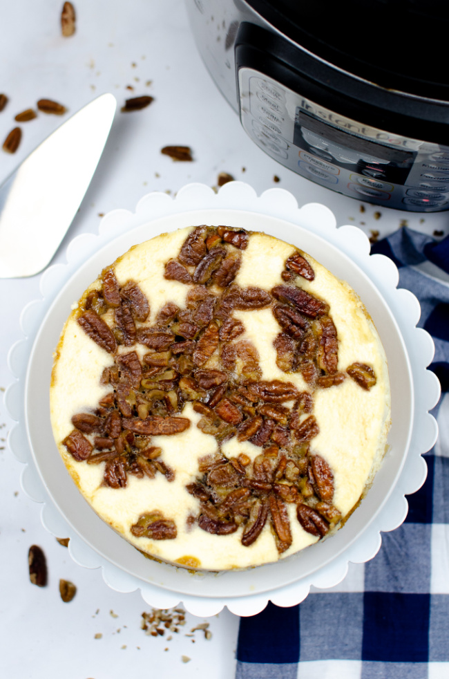 This photo features a Pecan Pie Cheesecake layed out on a white cake stand. A blue and white checkered tea towel is placed beside as a prop and in the background is an instant pot.
