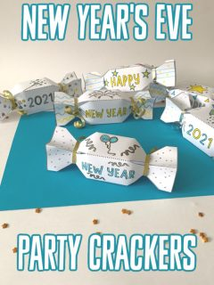 This photo features a blue paper background with some New Year's Eve Party Crackers colored and put together on top.