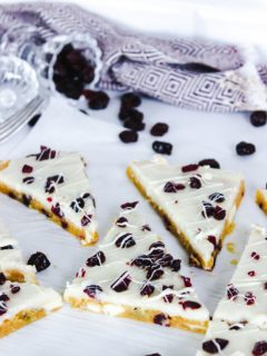 This image features Cranberry Bliss Bars layed out on a piece of parchment paper with craisins spread out around them and a purple tea towel in the background.