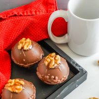 This photo features a tray of Turtle Hot Cocoa Bombs ready to be popped in the white mug on the side.