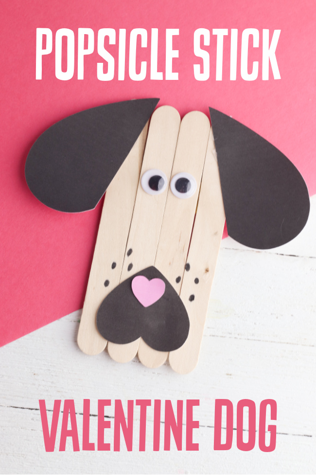 This photo features a created popsicle stick dog Valentine craft on top of a white and red background.