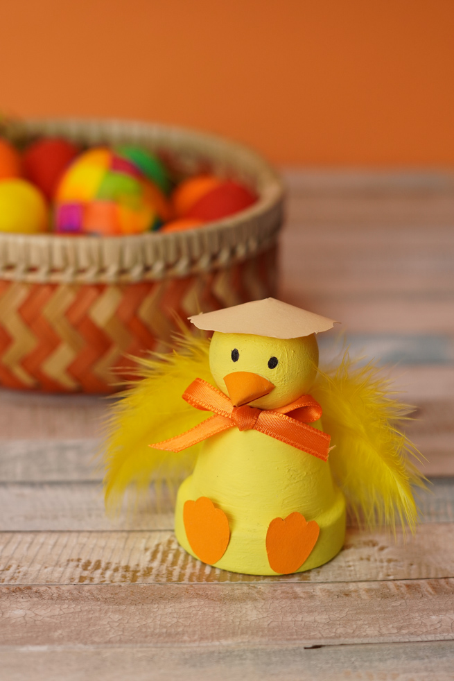 Easter chick terra cotta pot craft done up in yellow with a easter basket full of colorful eggs in back.
