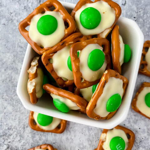 This photo features a marabled backdrop with a white bowl filled with green eggs and ham pretzels for Dr. Seuss's Birthday.