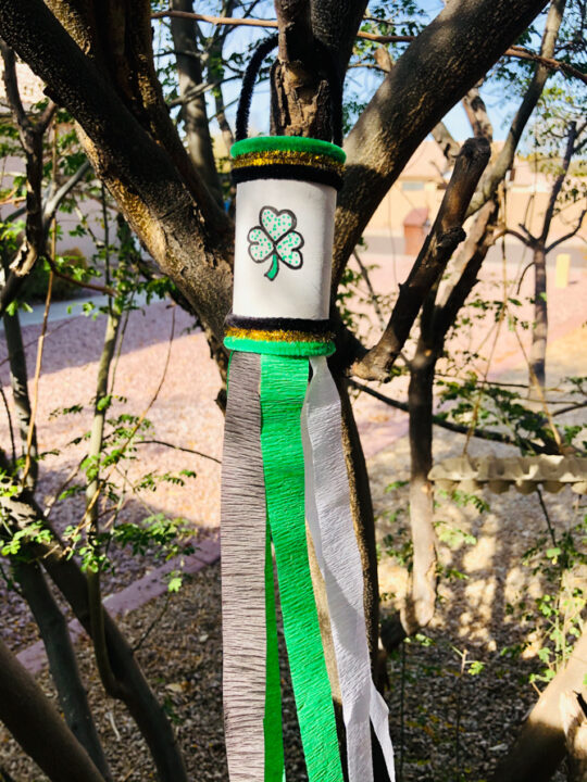 This photo features a completed St. Patrick's Day Windsock Toilet Paper Roll Craft hanging in a tree ready to catch the breeze from the wind.