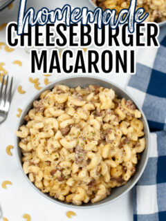 Homemade Cheeseburger Macaroni in a bowl with a blue and white tea towel to the right and a fork on the left.
