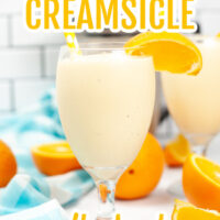 Orange Creamsicle Milkshake in a champagne style glass with a straw and slice of orange on the side.