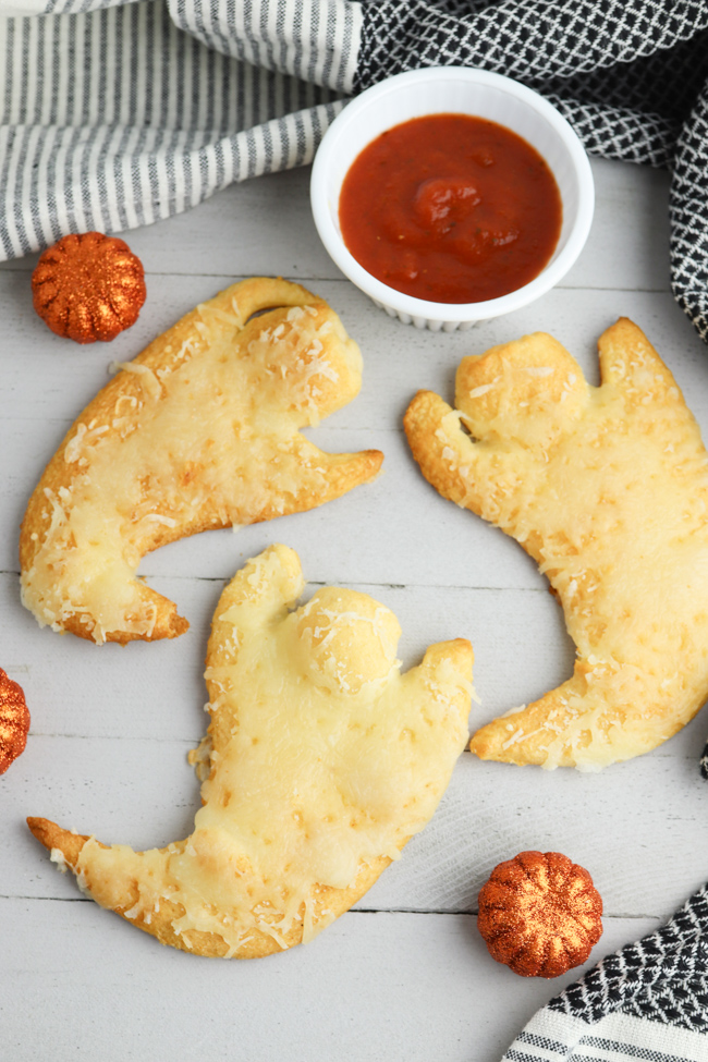 Cheesy Ghost Crescent Rolls on a white background with maranara dipping sauce